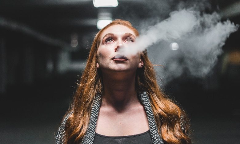 Woman in the act of vaping the electronic cigarette
